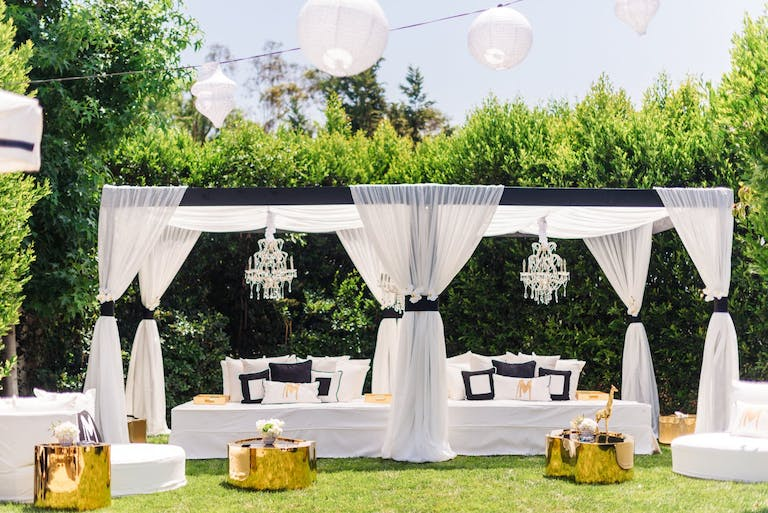Elegant White Cabanas With Black Bows, Chandeliers, and Gold Cocktail Tables for a Backyard Pool Party | PartySlate