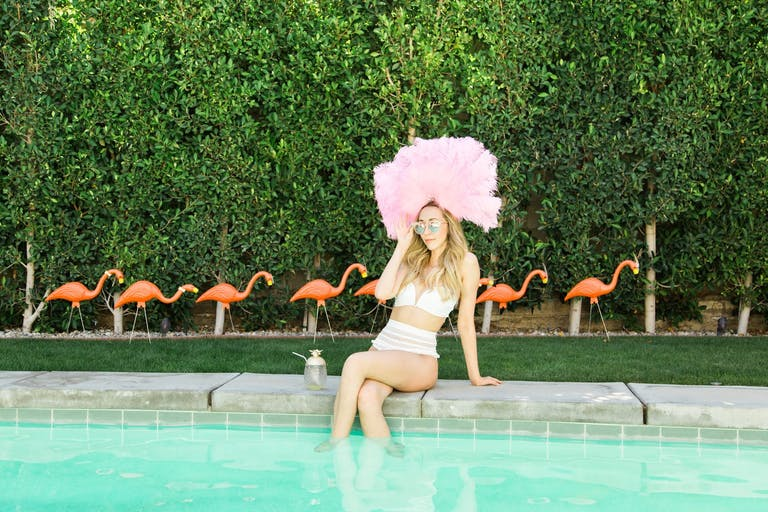 Girl in Bikini and Pink Feather Headdress Sits at Edge of Pool With Boxwood Backdrop and Row of Plastic Pink Flamingos | PartySlate