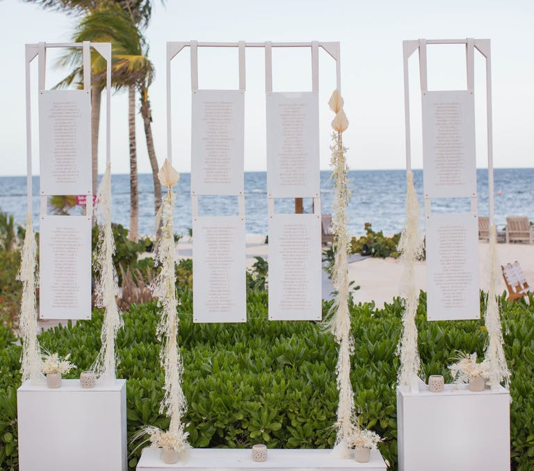 White Seating Chart Installation Against Tropical Beach Wedding Setting | PartySlate