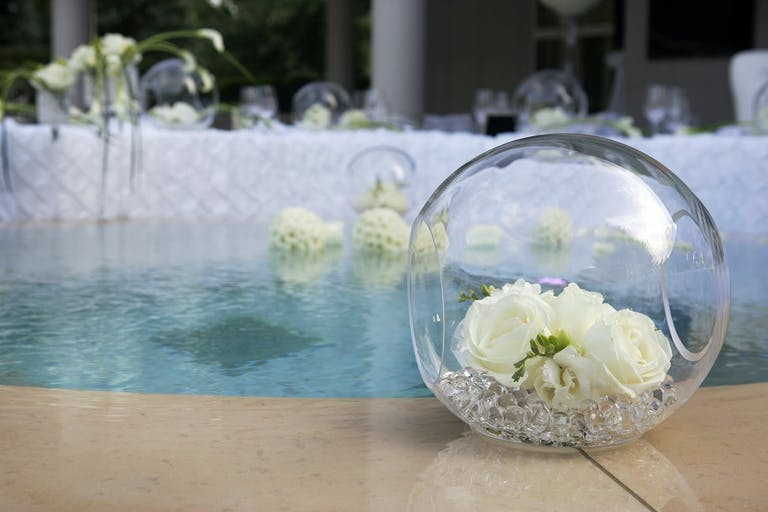 Poolside Décor With Glass Orbs Filled With White Flowers | PartySlate
