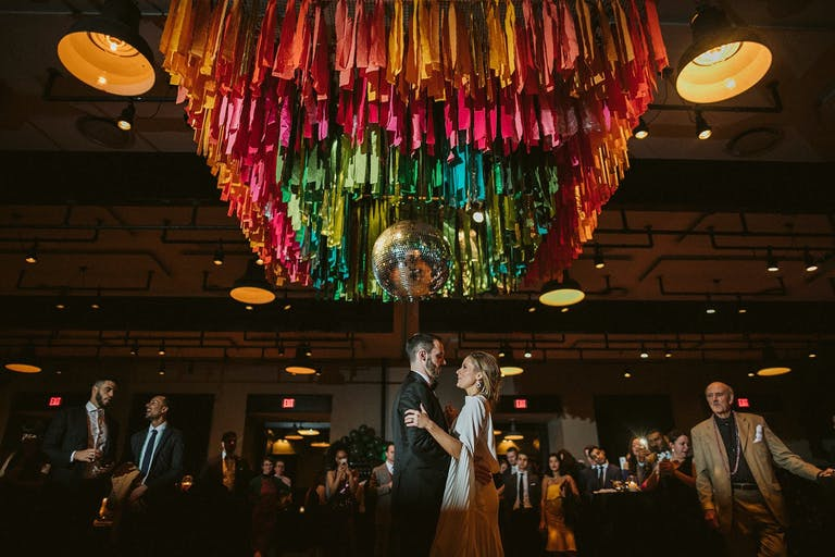 Bride and Groom Dance Beneath Wedding Ceiling Decorations of Rainbow Fringe Surrounding a Disco Ball | PartySlate