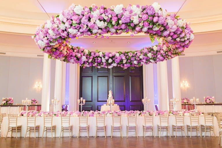 Wedding Ballroom in Peach and Neutral Tones With Suspended Giant Circular Wreathe of Pink and Purple Flowers | PartySlate