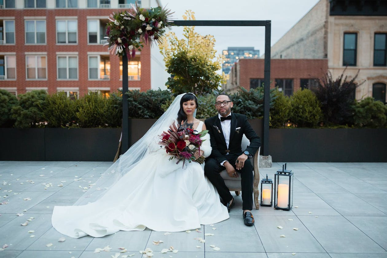 West Loop Chicago Wedding Venues: Bride and Groom Sit Under Minimalist Metal Arch With Lantern Décor and Greenery on Roof of Loft Lucia | PartySlate