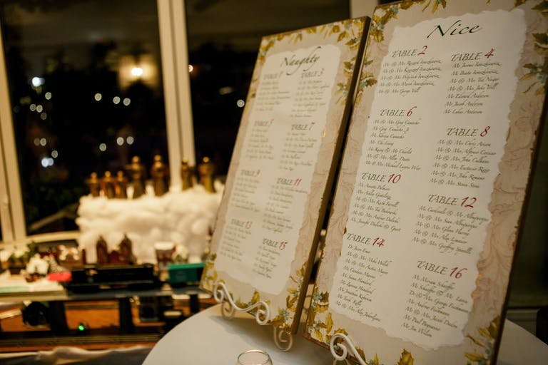 Gold-Edged Wedding Seating Chart With Poinsettia Designs for Christmas Wedding | PartySlate