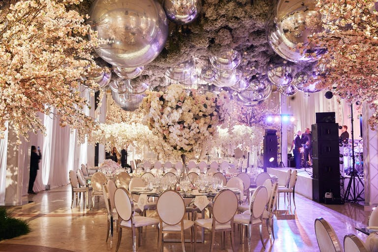 Luxuriant Wedding With Opulent Wedding Ceiling Decorations Consisting of Silver Balloons and White Florals | PartySlate