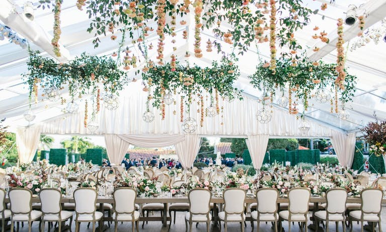 White Wedding Tent With Suspended Floral Fringe and Greenery Wreathes | PartySlate