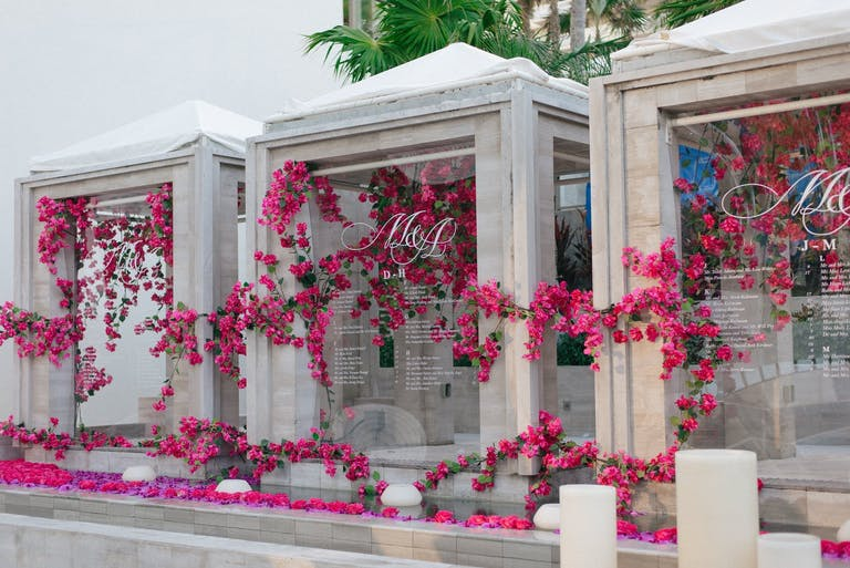 Three Acyrlic Wedding Seating Charts Covered in Pink Flowers at The Ritz-Carlton Bal Harbour | PartySlate