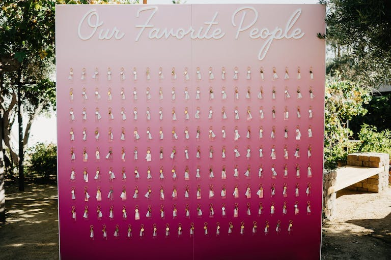 Wedding Seating Chart in Ombré Pink With Party Favor KeyChains Attached to Name Tags | PartySlate