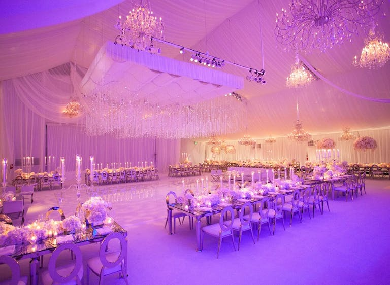 Tented Wedding with Suspended Crystal Ceiling Décor, Pink and Purple Uplighting, Polished Dance Floor, and Long Reception Tables | PartySlate