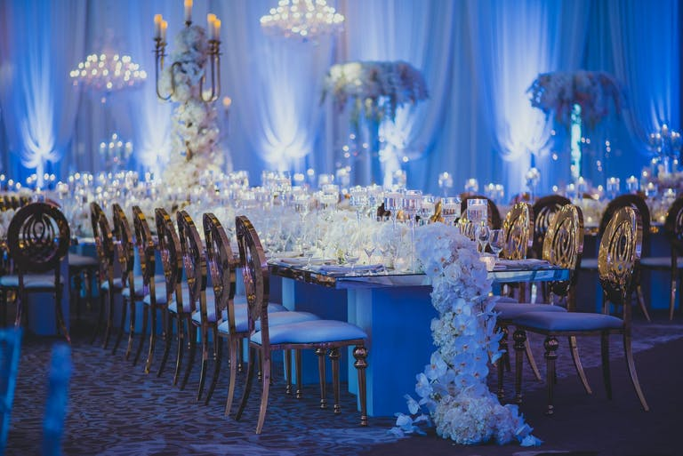Wedding Reception With Orchid Garland Centerpiece, Gold Seating, and Blue Uplighting   PartySlate