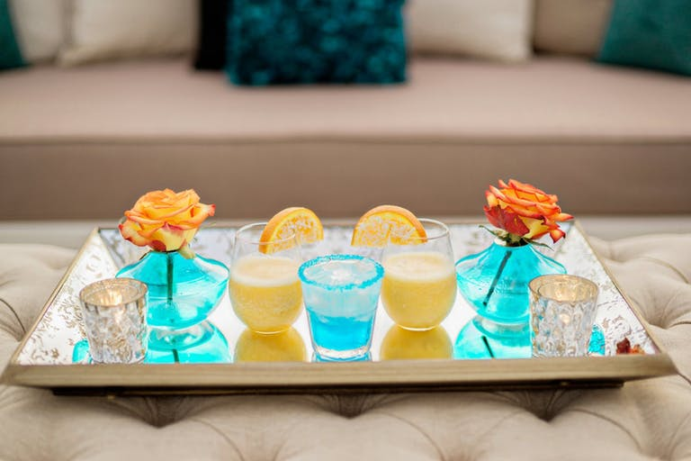 Blue and Yellow Summer Cocktails With Orange Roses in Blue Vases | PartySlate