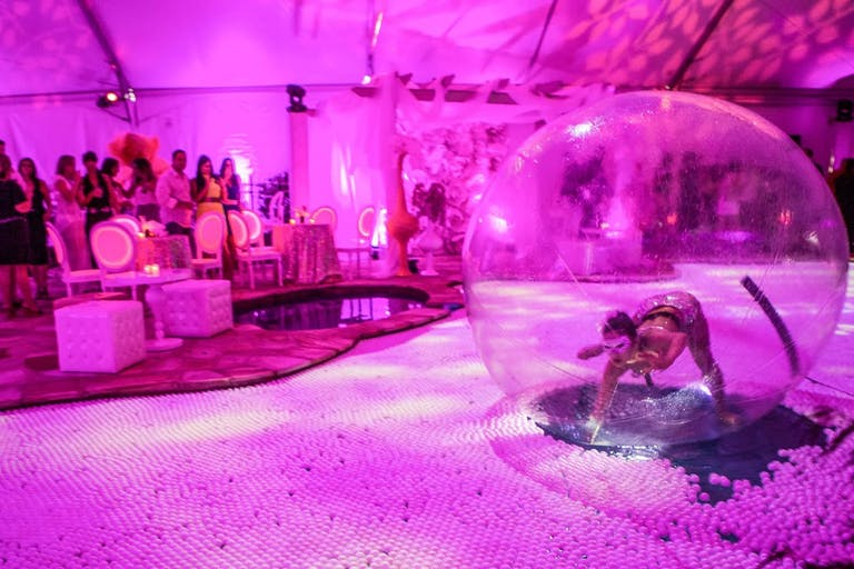 Dancer Performs in Bubble on Ping Pong-Filled Party Pool With Pink Uplighting | PartySlate