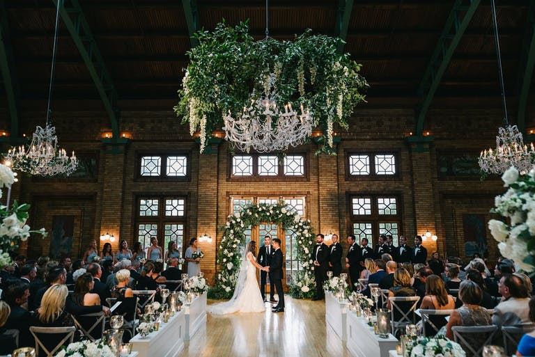 Wedding Ceremony at Cafe Brauer at Lincoln Park Zoo With Glittering Chandelier With Cascading Tendrils of Greenery | PartySlate