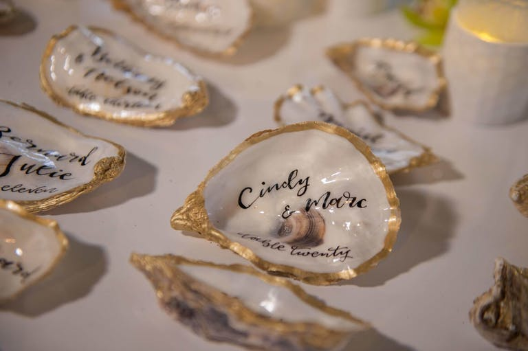 Table of Golden-Edged Oysters Inscribed With a Name and Wedding Table Number | PartySlate
