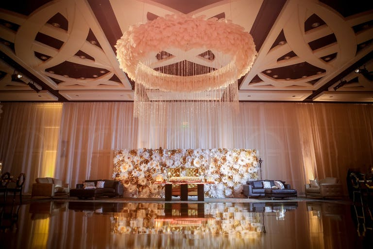 Wedding Reception With Mirrored Dance Floor, Floral-Backed Stage, and Suspended Ring of Pink Flowers from Ceiling | PartySlate