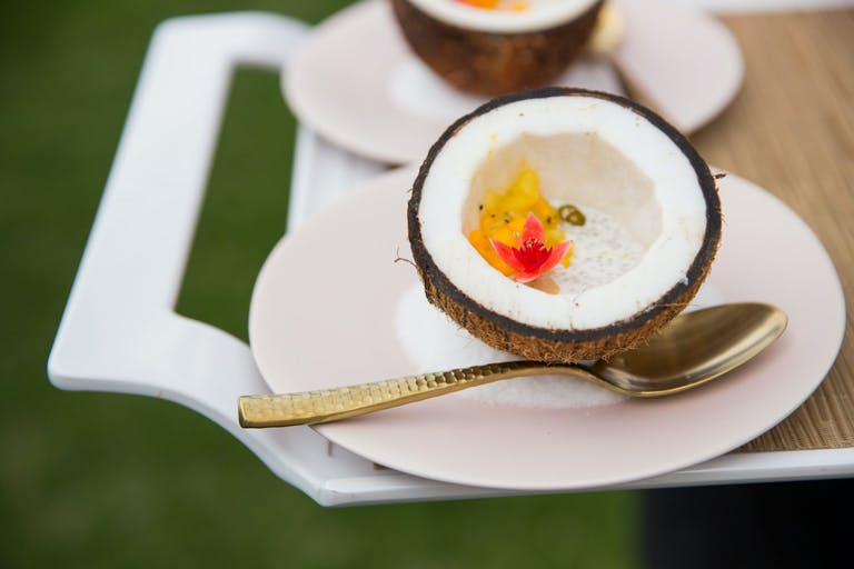 Half of Coconut With Bright Orange Flower and Spoon on White Plate | PartySlate