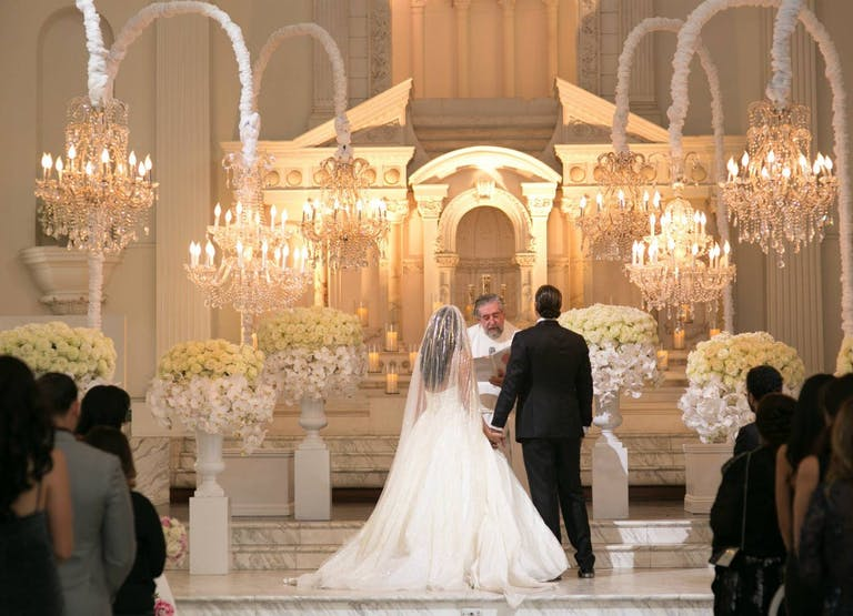 Bride and Groom Exchange Vows Before Officiant and Guests in All-White Ballroom With Chandeliers Suspended From White Curved Poles | PartySlate