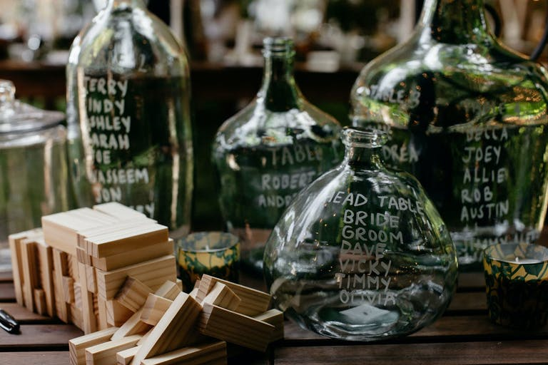 Table With Vintage Glass Jars Inscribed With Wedding Table Numbers and Guests' Names | PartySlate
