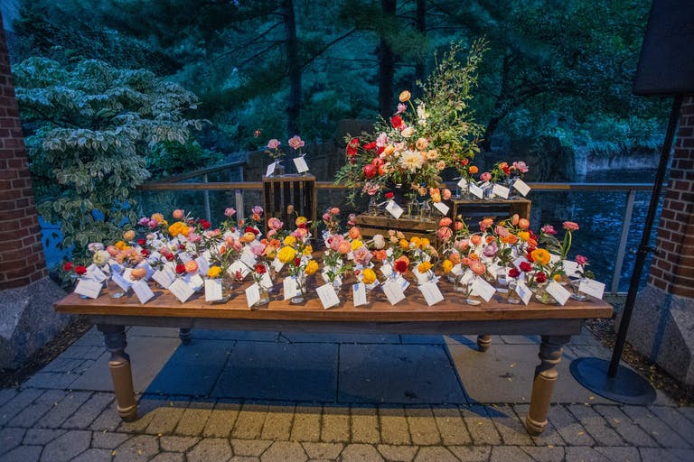 Central Park Zoo Evening Wedding With Wooden Table, Colorful Flowers, and White Escort Cards | PartySlate