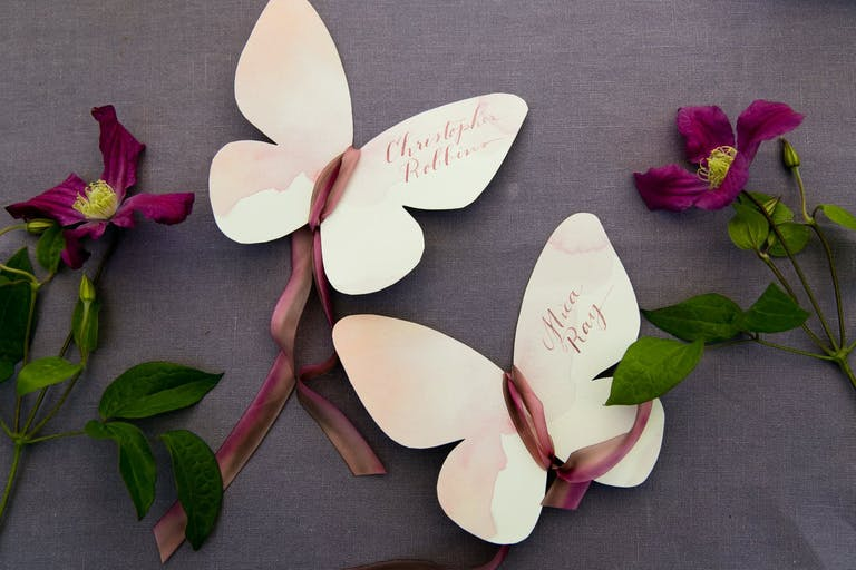 Paper Butterfly Wedding Escort Cards With Mauve Ribbon and Greenery | PartySlate