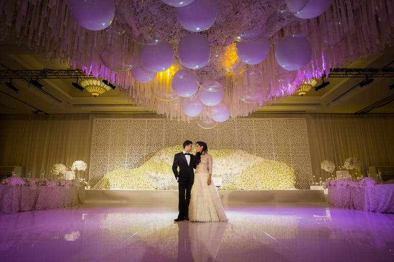 Bride and Groom Stand on Purple-Lit Dance Floor and Under Wedding Ceiling Decorations With Shimmering Balloons | PartySlate