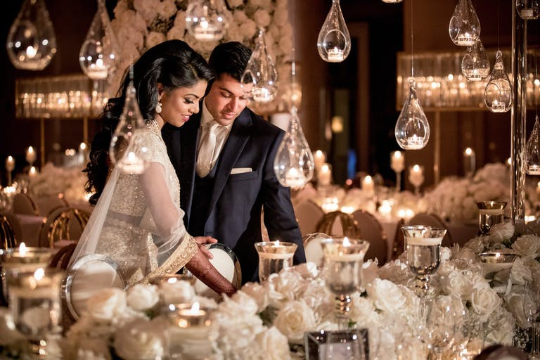 Bride and Groom Share a Moment at White Wedding Tablescape and Suspended Globed Candlelight   PartySlate