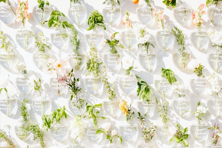 Wedding Seating Backdrop With Inscribed Vases and Bright Flowers | PartySlate