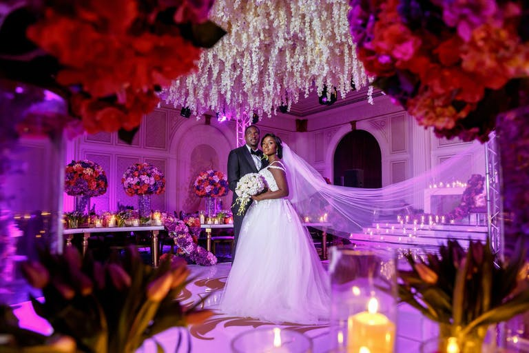 Ceiling of Suspended White Flowers With Red Rose Centerpieces in Foreground | PartySlate