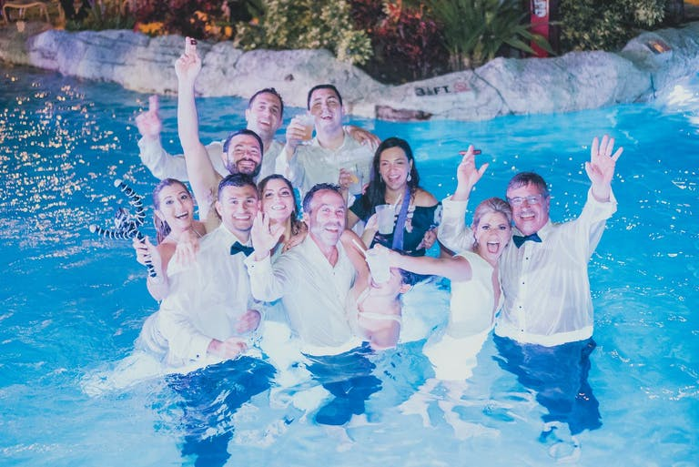 Wedding Party Poses After Jumping in Pool at End of Celebration | PartySlate