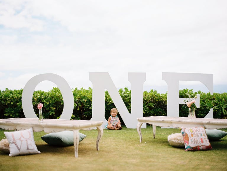 Baby Sits in Front of Numbered Signage at Outdoor Kids Birthday Party With Low Table Seating and Throw Pillow Cushions | PartySlate