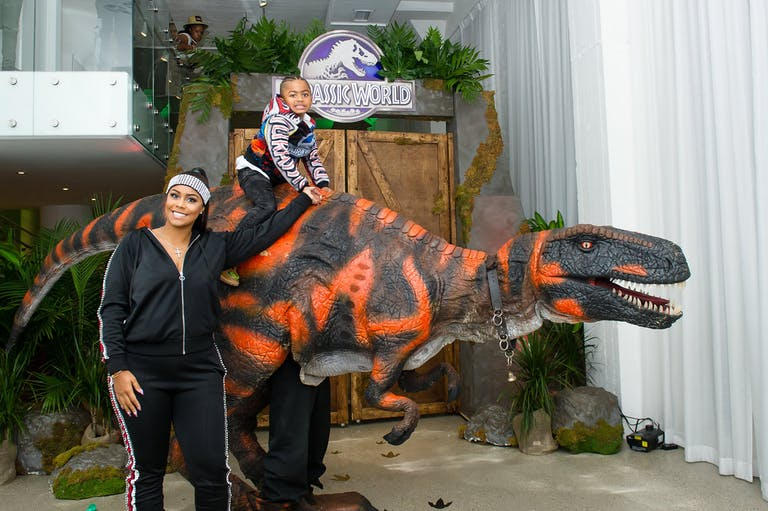 Little Boy Sitting On Top a Life-Like Dinosaur at 5th Jurassic Dinosaur Themed Birthday Party | PartySlate