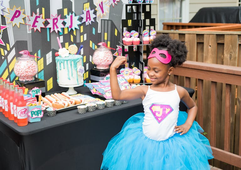 Little Girl Standing In Front of Dessert Table at Superhero Themed Kids 8th Birthday Party with Themed Food and Costumes | PartySlate