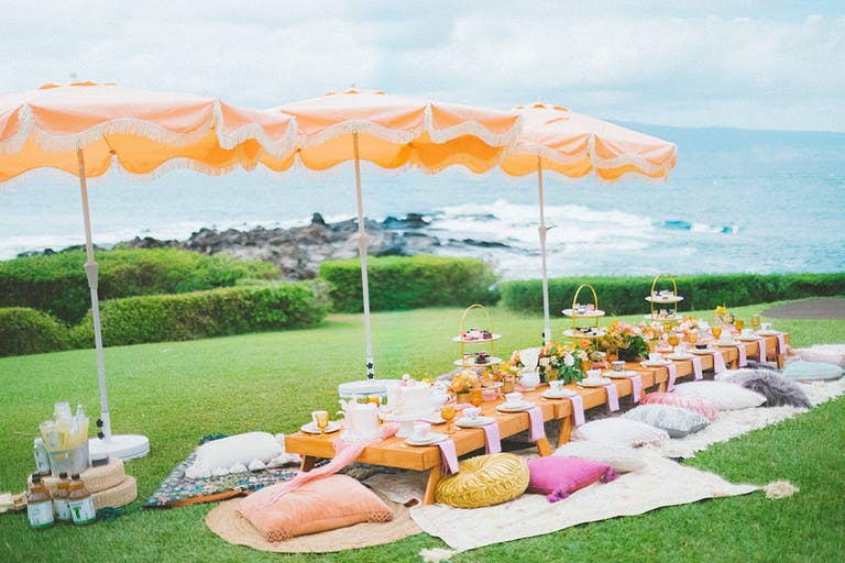 Tropical Orange Pink and White Oceanfront High Tea Party at Montage Kapalua Bay in Kapalua, HI with Ocean in the Background and Pillows on the Ground Around a Low Table with Umbrellas | PartySlate