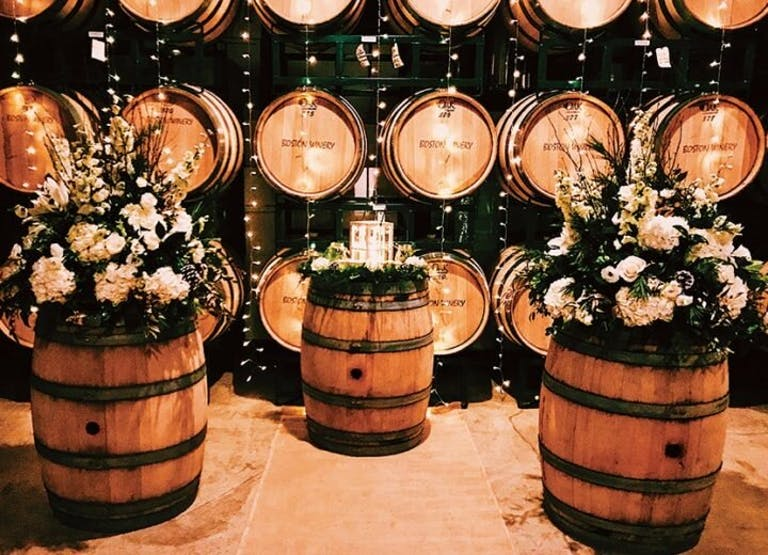 Tasting room full with barrels of wine and flower on them | PartySlate