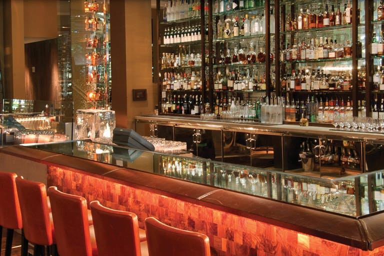 BOURBON STEAK Bar With Orange Seating and Glass Shelving | PartySlate