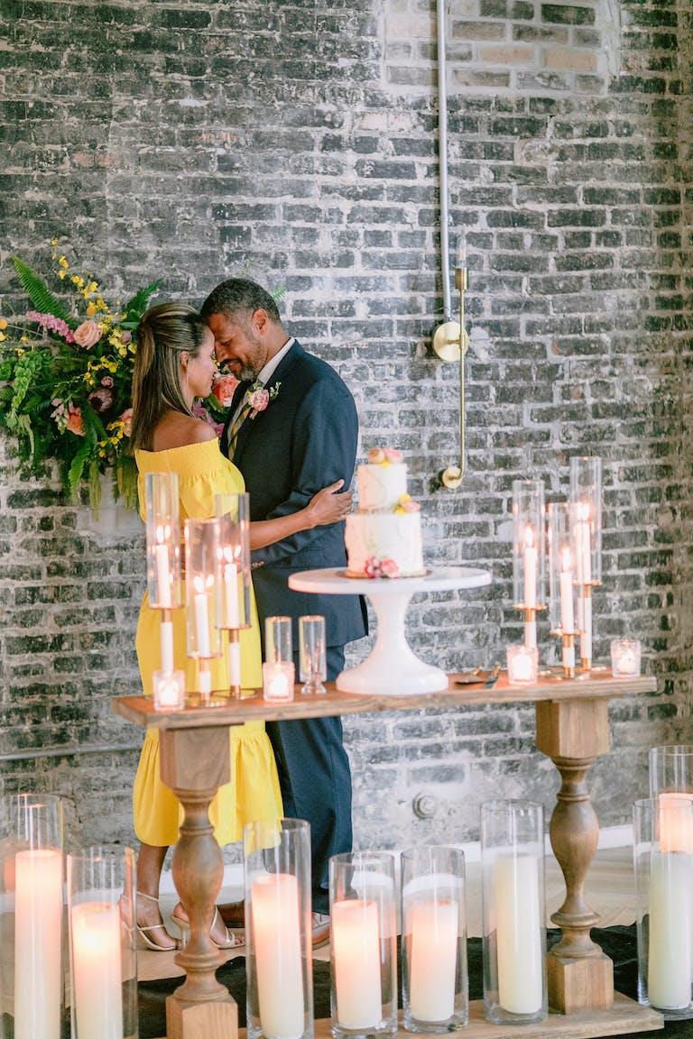 Couple Pose Behind Candlelit Cake Station   PartySlate
