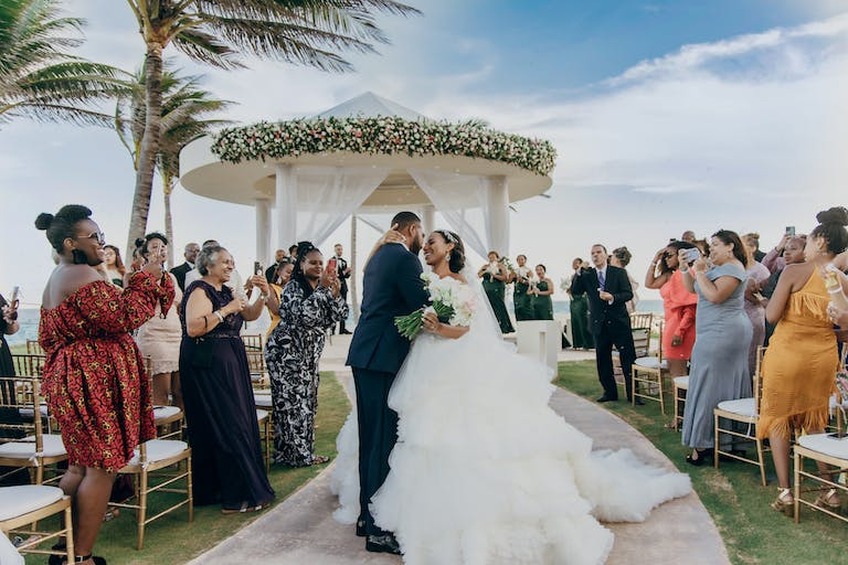 Bride and Groom Kiss During Recessional Walk With Floral-Wrapped Circular White Arbor in Background | PartySlate