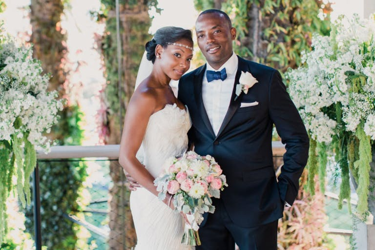 Bride and Groom Pose Before Lush Backdrop of Greenery | PartySlate