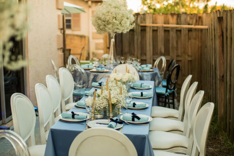 Tablescape With Light Blue Linen, White Modern Seating, and Baby's Breath Centerpieces | PartySlate