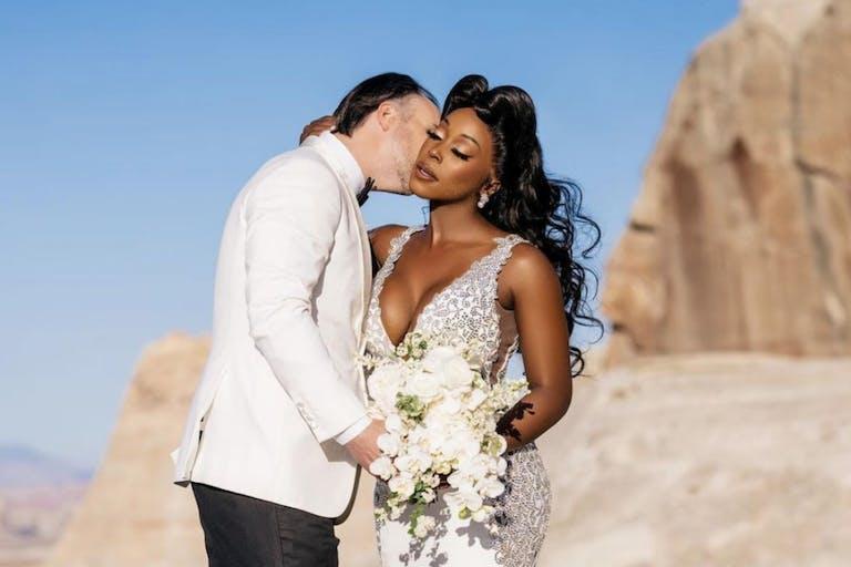 Groom Kisses Bride Against Desert Backdrop With Deep Blue Sky | PartySlate