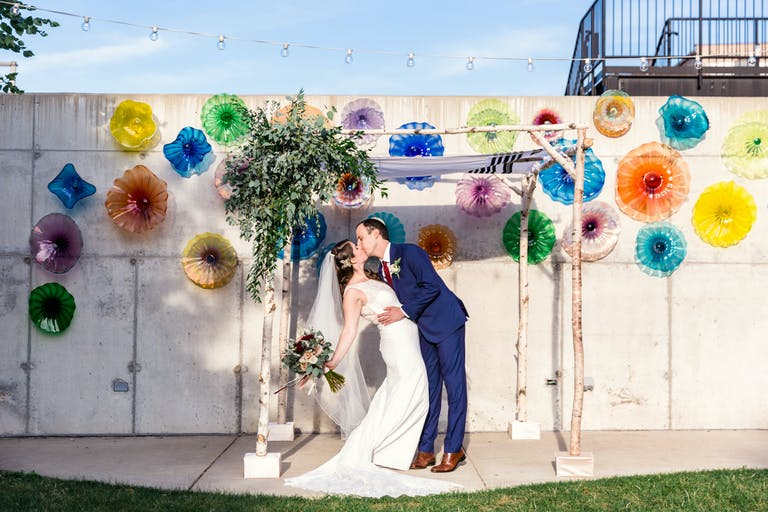 Bride and Groom Kiss Beneath Chuppah in Funky and Colorful Urban Garden at Ignite Glass Studios in Chicago, IL   PartySlate
