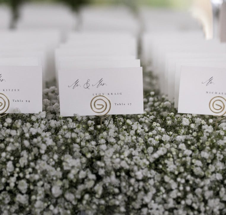 White Wedding Seating Cards on a Bed of Baby's Breath