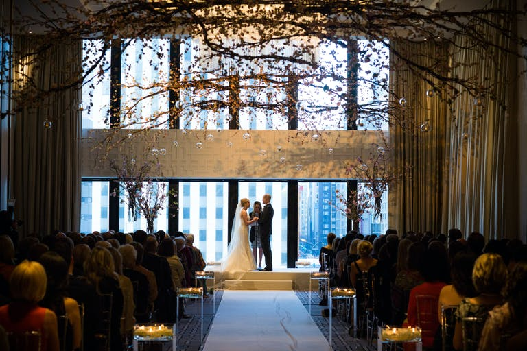Bride and Groom Exchange Vows Indoors at The Langham, Chicago With Floor-to-Ceiling Windows and Overarching Branches   PartySlate