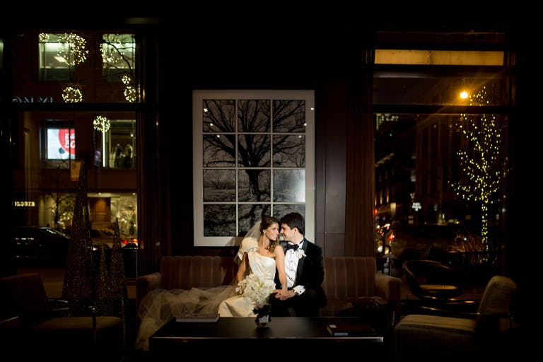 Bride and Groom Sit on Sofa at Park Hyatt Chicago In Dim Room With Wood Paneled Walls   PartySlate