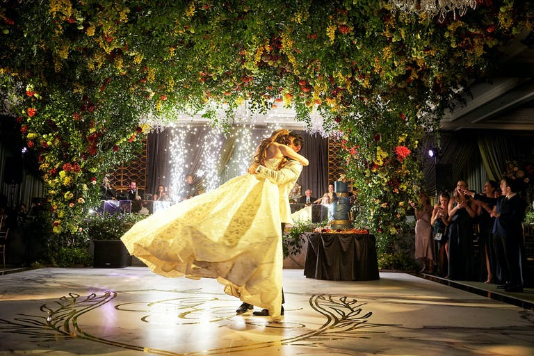 Groom Picks Up Bride on Dance Floor Under Arched Greenery at Four Seasons Hotel Chicago   PartySlate