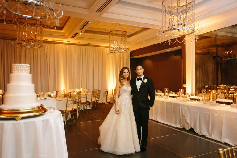 Bride and Groom Stand Behind White Wedding Cake in Ballroom at Waldorf Astoria Chicago Hotel   PartySlate