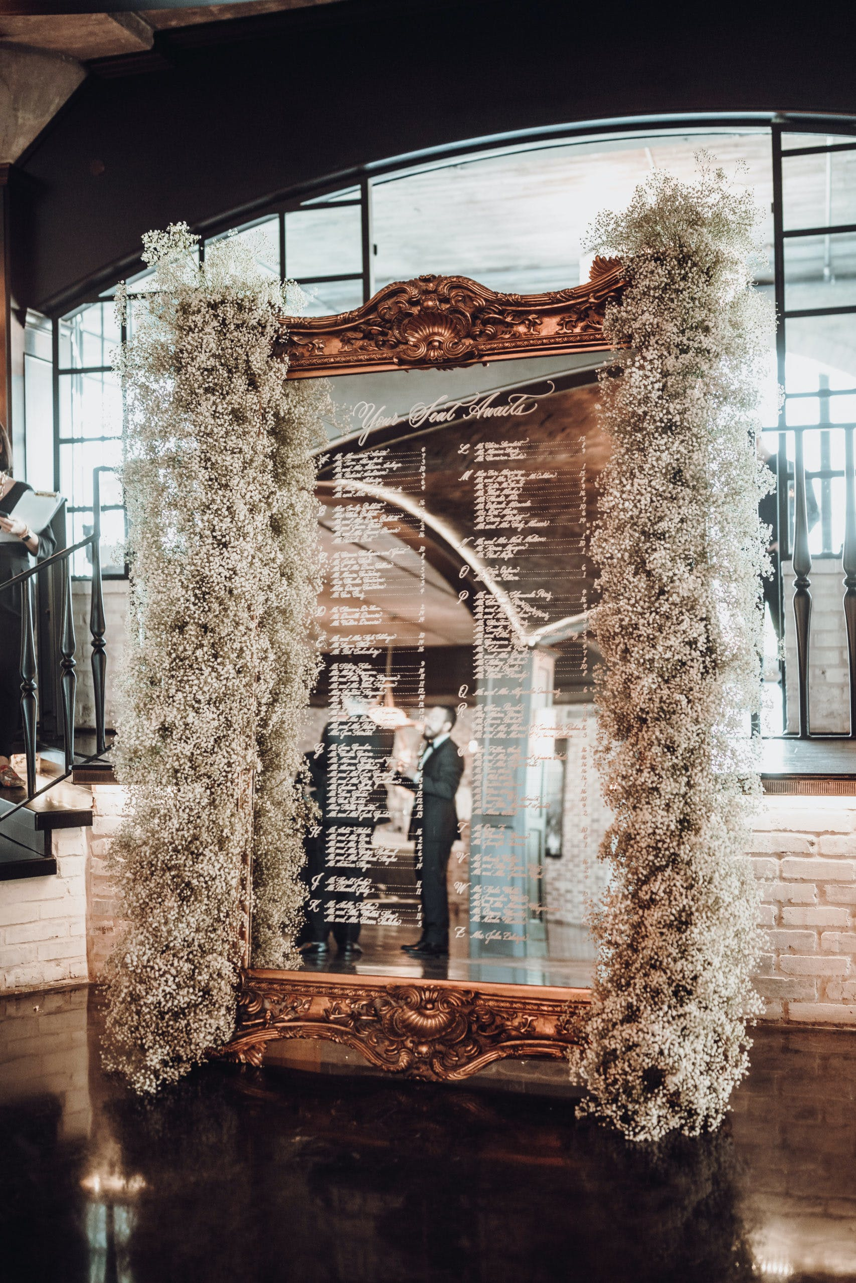 Giant Ornately-Framed Gold-Mirrored Wedding Seating Chart Flanked in Baby's Breath   PartySlate