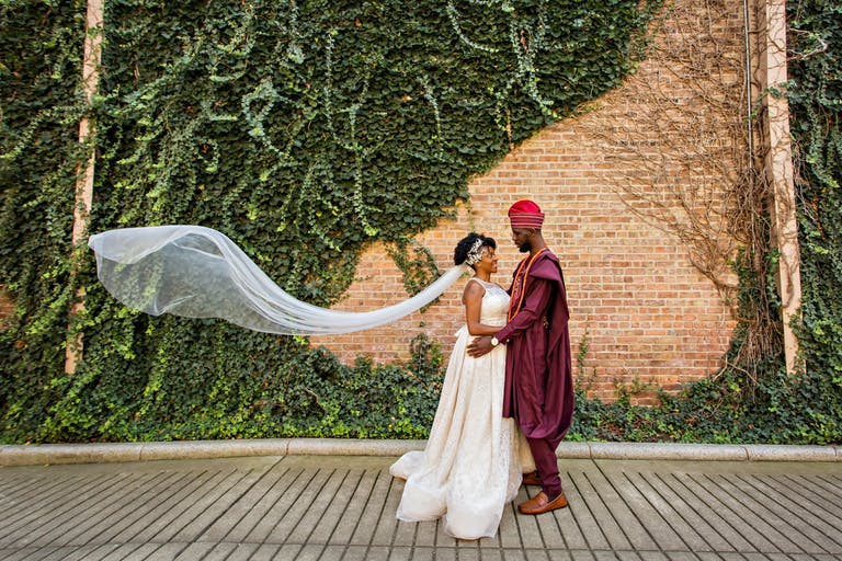 Bride and Groom Wear Traditional Nigerian Attire With Ivy Covered Wall at Glessner House in Chicago in Backdrop   PartySlate