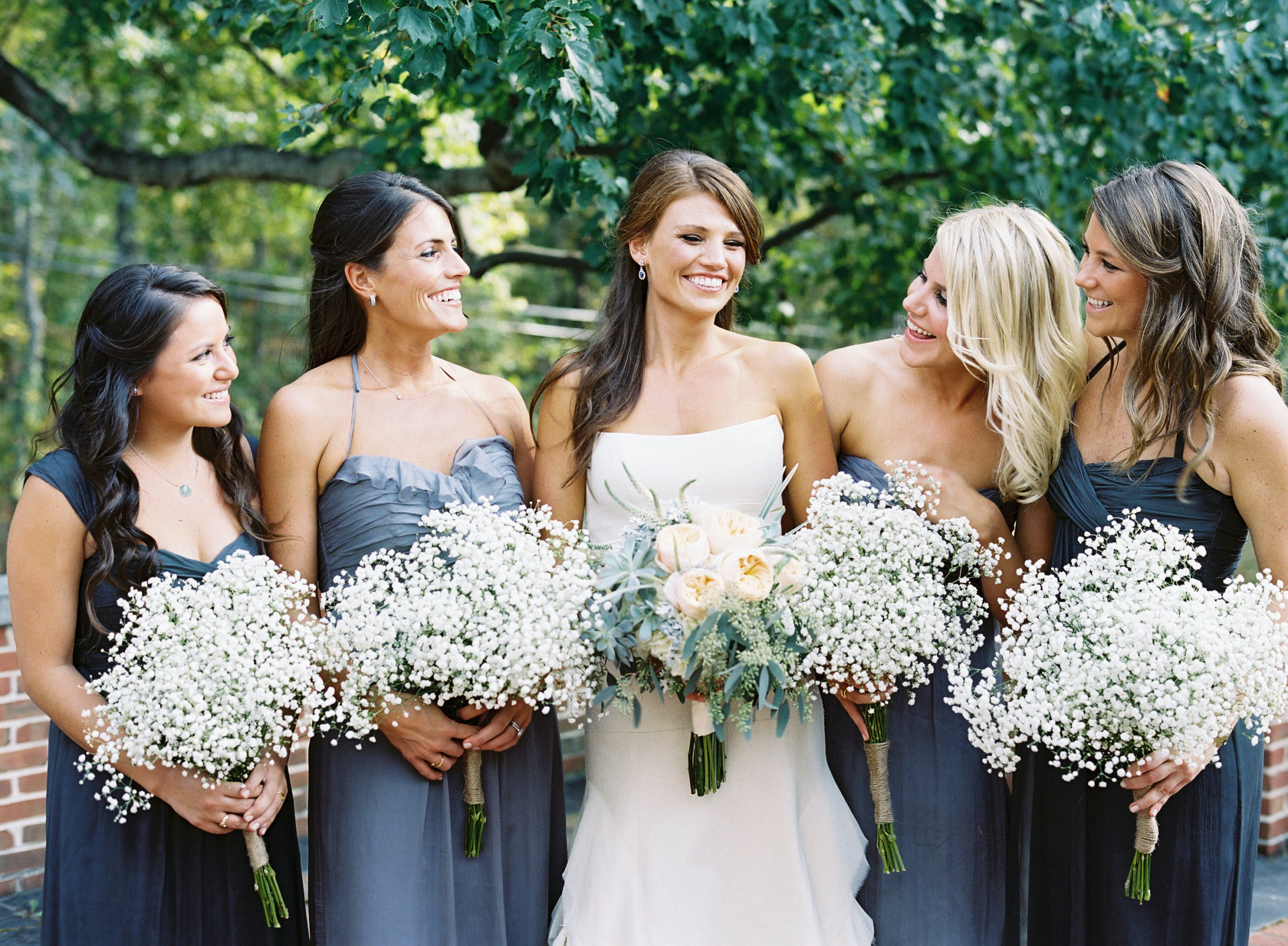Bride is flanked by two bridesmaids on each side holding baby's breath wedding bouquets   PartySlate
