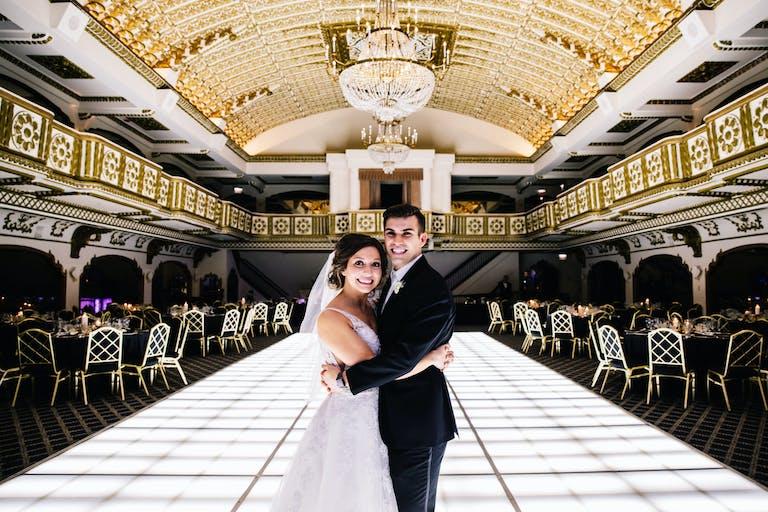 Bride and Groom Embrace on White LED Dance Floor in Opulent Ballroom at Millennium Knickerbocker Hotel